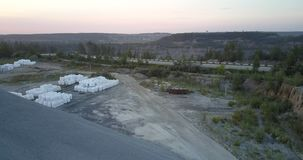 White bags clusters against grey road in summer evening. Loaded white bags clusters against grey road with rubble barrow on foreground in summer evening dusk stock footage