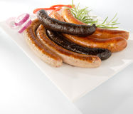 White baked sausage and grilled black pudding. Isolated on a plate with white background royalty free stock images