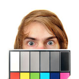White Balance Color Card. A male production assistant holds up a white balance card with test colors on it to calibrate the colors for photography and Stock Photos