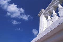 White Balcony. Corner of a white balcony. Summer sky with pieces of cloud as backdrop Stock Photos