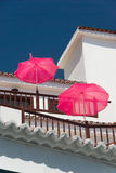 White balcony house with pink parasols on a background of blue sky Stock Images