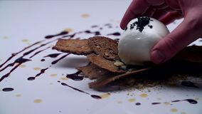 A white ball is laid over the black bread on a white table. The cook holds a white edible ball with two fingers. Close-up stock footage