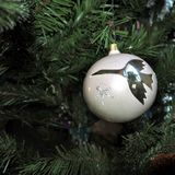 White ball with a picture of crane. vintage christmas toys on new year tree background. stock images