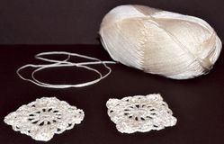 White ball of yarn and knitting patterns of lace on the brown surface.  royalty free stock photo