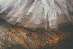 White ballet tutu on wooden floor. Retro filtered. And toned royalty free stock image