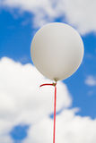 White ballon in the sky. A white balloon floating against a blue sky with fluffy white clouds. Red ribbon stock photos
