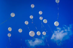 White balloons on the blue sky Stock Photos