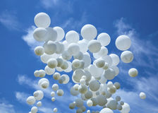 White balloons on the blue sky Stock Image
