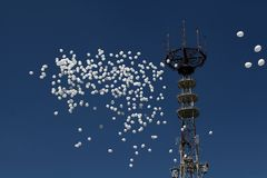 White balloons fly against the background of a television tower in the city of Minsk, Belarus royalty free stock photo