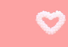 White balloons in the form of heart on a pink background