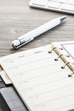 White ballpoint pen and leather weekly calendar. On brown wooden table Royalty Free Stock Image