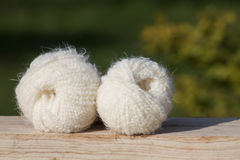 White balls of soft wool on wooden board. Green background Stock Images