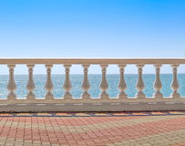 White baluster overlooking the sea. White baluster overlooking sea horizon and clear sky stock image