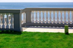 White balustrades with gray railings and a marble walkway. White balustrades with gray railings and a marble walkway with a green lawn, descent to the sea of an stock image