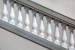 White balustrades handrails of gray stone stairs. White balustrades handrails of gray stone stairs, closeup of details of architecture illuminated by the sun stock image