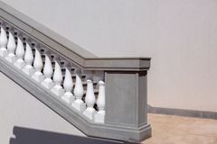 White balustrades with handrails of gray stone stairs. White balustrades with handrails of gray stone stairs and marble floor, close up of details of stairs by stock images