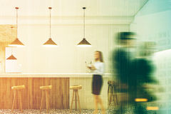 White bar interior, stools, people. People in a white bar interior with a white and wooden bar stand, rows of wooden stools and low hanging lamps. 3d rendering Stock Photos