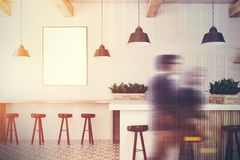 White wooden bar, white stand and poster toned. White bar interior with a wooden bar stand, a row of dark wooden chairs and a framed vertical poster on a wall Stock Photography