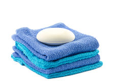 White bar of soap on top of towels Royalty Free Stock Images