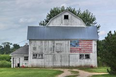 White barn with American flag. An old white barn against a stormy sky with a flag emblazoned on it Stock Photo