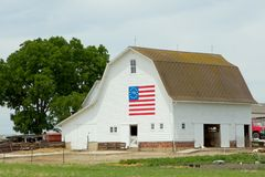 White Barn With Centennial Flag. White barn with centennial American flag in the Midwestern United States royalty free stock image