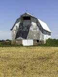 A white barn in a field. A painted white wooden barn in a field on a beautiful summer day royalty free stock photos