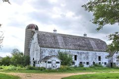 White barn and silo. An old white barn with the paint peeling and an abandoned silo against a stormy sky Royalty Free Stock Images