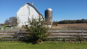 White Barn and Silo with a Wooden Fence stock photography