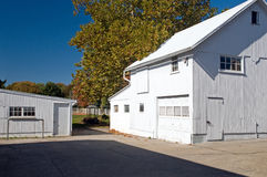 White barns and workshop. A view of two white barns or garages in a barnyard Royalty Free Stock Images
