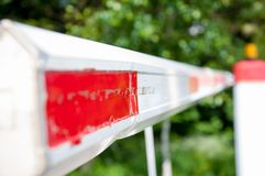 White barrier with red stripes on the background of green trees. royalty free stock photography