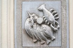 White bas-relief figure of a fish and a lobster. Royalty Free Stock Image