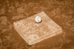 Image of a baseball on a dirt covered third base. royalty free stock photo