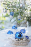 White basket with decorative xmas balls on the snow and blue balls on christmas tree Royalty Free Stock Image