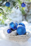 White basket with decorative xmas balls on the snow and blue balls on christmas tree. Outdoors in bright sunshine Stock Images