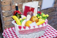 White Basket with  fruits and wine bottles on a red checkered tablecloth Royalty Free Stock Photo