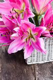 White  basket with pink lily flowers bouquet on rustic wooden ta. Ble Royalty Free Stock Photos