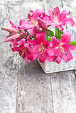 White basket with pink lily flowers bouquet on rustic wooden tab. White basket with pink  lily flowers bouquet on rustic wooden table Royalty Free Stock Image