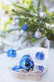 White basket with xmas balls outdoors in bright sunshine. White basket with decorative xmas balls on the snow and blue balls on christmas tree outdoors in bright stock image