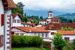 White basque houses in Pyrenees mountains, Saint Jean Pied de Po. Traditional white houses and church in a basque village in the Pyrenees mountains on spanish royalty free stock images