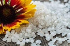 White bath salt. Yellow flower. Sea salt royalty free stock photo
