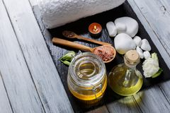 Bath towel, honey, aroma oil, candles, flowers and pebbles for spa and aroma procedures on a dark board. White bath towel, bee honey, aroma oil, burning small Royalty Free Stock Photography