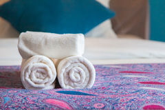 White bath towel rolled up on a bed in hotel room. Stock Images