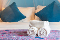 White bath towel rolled up on a bed in hotel room. Stock Photos