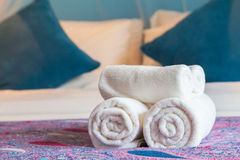 White bath towel rolled up on a bed in hotel room. Royalty Free Stock Photography