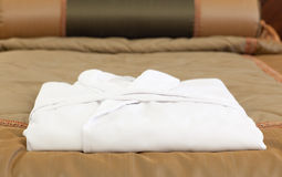 White bathrobe on the hotel bed Stock Image