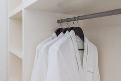 White bathrobe with wooden hangers in wardrobe Royalty Free Stock Photo
