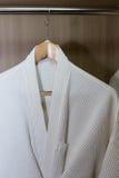 White bathrobes hanging Stock Images