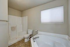 White bathroom interior with corner bathtub and shower . Northwest, USA Stock Photo