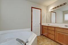 White bathroom interior with corner bathtub and vanity cabinet. Royalty Free Stock Images