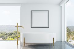 Original bathroom with a poster. White bathroom interior with panoramic windows, a tropical view, an originally shaped bathtub and a framed square poster on a Stock Photos